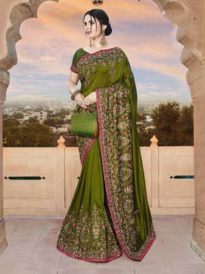 For A Royal Look, Grab This Heavy Designer Saree In Olive Green Color Paired With Olive Green Colored Blouse. This Saree And Blouse Are Silk Based Beautified With Heavy Embroidery. This Lovely Saree Is Suitable For Wedding And Party Wear.