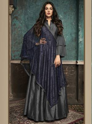 Enhance Your Personality Wearing This Designer Floor Length Suit In Dark Grey Color Paired With Contrasting Navy Blue Colored Heavy Dupatta. Its Elegant Floor Length Top Is Fabricated On Art Silk Paired With Santoon Bottom And Net Fabricated Dupatta Beautified With Heavy Stone Work.