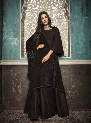 For A Bold And Beautiful Look, Grab This Designer Floor Length Suit In Dark Brown Color Paired With Black Colored Dupatta. Its Top Is Fabricated On Art Silk Paired With Santoon Bottom And Brasso Dupatta. Its Bold Color And Attractive Brasso Pattern Will Earn You Lots Of Compliments From Onlookers.