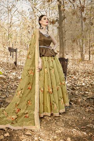 Here Is A Tendy Designer Lehenga Choli In Peplum Pattern With Brown Colored Blouse Paired With Contrasting Olive Green Colored Lehenga And Dupatta. Its Blouse Is Fabricated On Art Silk Paired With Orgenza Based Lehenga And Dupatta. Buy This Trendy Piece Now.