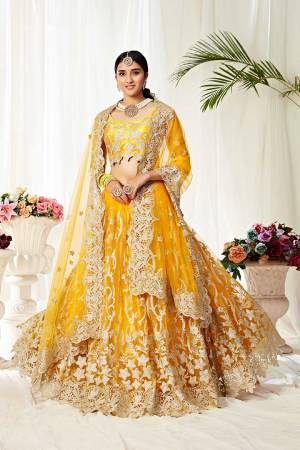 Heavy Designer Lehenga Choli In Yellow Color Fabricated On Net Beautified With Heavy Attractive Embroidery.