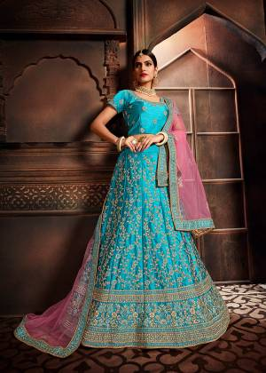 Add This Beautiful Lehenga Choli To Your Wardrobe For This Festive Season With This Lovely Blue Colored Lehenga Choli Paired With Contrasting Pink Colored Dupatta. This Lehenga Choli Is Silk Based Paired With Net Fabricated Dupatta. Buy Now.