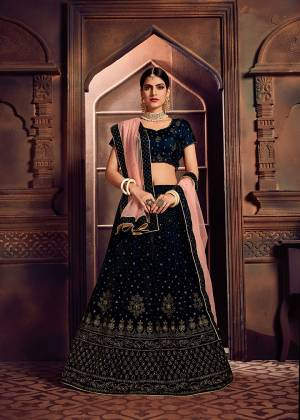 You Will Definitely Earn Lots Of Compliments In This Elegant Looking Designer Lehenga Choli In Navy Blue Color Paired With Peach Colored Dupatta. This Beautiful Lehenga Choli Is Fabricated On Velvet Paired With Net Fabricated Dupatta. It Is Beautified With Attractive Stone Work All Over.