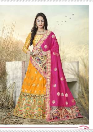 This Festive Season Have A Proper Traditional Look Wearing This Silk Based Lehenga Choli In Musturd Yellow Color Paired With Contrasting Rani Pink Colored Dupatta. This Lehenga Choli Is Fabricated On Banarasi Jacquard Silk Beautified With Weave All Over.