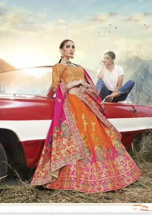 This Festive Season Have A Proper Traditional Look Wearing This Silk Based Lehenga Choli In Orange Color Paired With Contrasting Rani Pink Colored Dupatta. This Lehenga Choli Is Fabricated On Banarasi Jacquard Silk Beautified With Weave All Over.