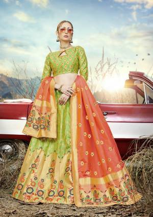 Look Pretty In This Designer Silk Based Lehenga Choli In Light Green Color Paired With Contrasting Orange Colored Dupatta. It Is Fabricated On Banarasi Jacquard Silk Beautified With Weave All Over. Buy This Pretty Piece Now.?
