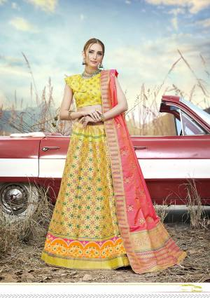 This Festive Season Have A Proper Traditional Look Wearing This Silk Based Lehenga Choli In Yellow Color Paired With Contrasting Pink Colored Dupatta. This Lehenga Choli Is Fabricated On Banarasi Jacquard Silk Beautified With Weave All Over.