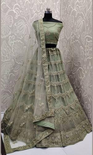 This Wedding Season, Look The Most Graceful Of All Wearing This Heavy Designer Elegant Lehenga Choli In Olive Green Color. Its Blouse, Lehenga And Dupatta are Fabricated on Net Beautified With Tone To Tone Coding And Resham Embroidery With Stone Work. Buy Now.