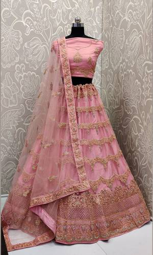 This Wedding Season, Look The Most Graceful Of All Wearing This Heavy Designer Elegant Lehenga Choli In Pink Color. Its Blouse, Lehenga And Dupatta are Fabricated on Net Beautified With Tone To Tone Coding And Resham Embroidery With Stone Work. Buy Now.