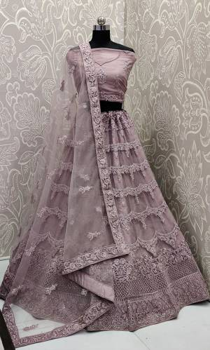 This Wedding Season, Look The Most Graceful Of All Wearing This Heavy Designer Elegant Lehenga Choli In Mauve Color. Its Blouse, Lehenga And Dupatta are Fabricated on Net Beautified With Tone To Tone Coding And Resham Embroidery With Stone Work. Buy Now.