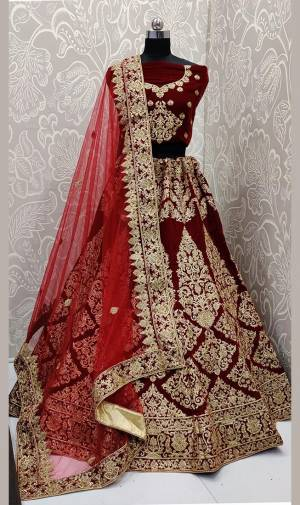 Here Is A Beautiful Designer Bridal Lehenga Choli In Maroon Color Paired With Red Colored Dupatta. This Beautiful Heavy Lehenga Choli Is Fabricated On Velvet Paired With Net Fabricated Dupatta. It Is Beautified With Heavy Detailed Embroidery. Get Ready For Your D-Day With This Designer Piece And Look The Most Graceful Of All.