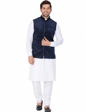 Here Is A Rich And Decent Looking Readymade Pair Of Men's Kurta Pyjama In White Color Paired With Navy Blue Colored Jacket. This Kurta And Pyjama Are Fabricated On Cotton Paired With Velvet Fabricated Jacket. Buy This Pair For The Upcoming Wedding And Festive Season.