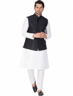 Here Is A Rich And Decent Looking Readymade Pair Of Men's Kurta Pyjama In White Color Paired With Black Colored Jacket. This Kurta And Pyjama Are Fabricated On Cotton Silk Paired With Art Silk Fabricated Jacket. Buy This Pair For The Upcoming Wedding And Festive Season.