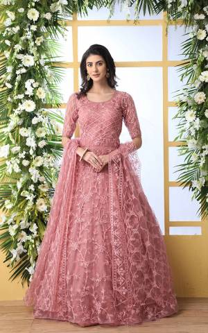 Look Pretty In This Designer Floor Length Gown In Pink Color Paired With Peach Colored Dupatta. Its Heavy Embroidered Top Is Fabricated On Net Paired With Net fabricated Dupatta. Buy This Semi-Stitched Designer Gown Now.