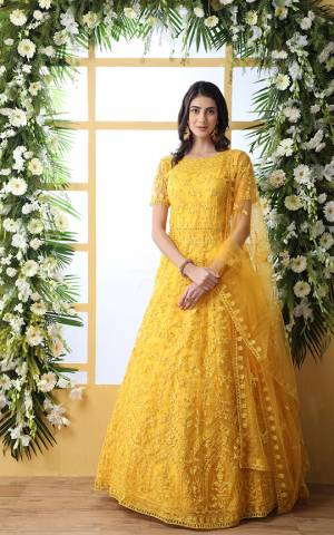 Look Pretty In This Designer Floor Length Gown In Yellow Color Paired With Peach Colored Dupatta. Its Heavy Embroidered Top Is Fabricated On Net Paired With Net fabricated Dupatta. Buy This Semi-Stitched Designer Gown Now.