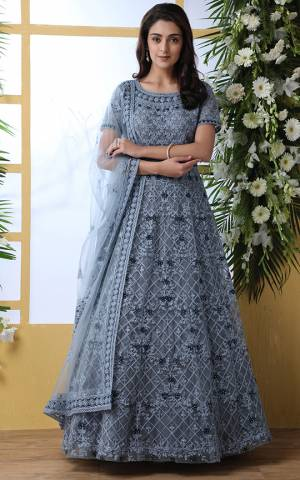 Look Pretty In This Designer Floor Length Gown In Grey Color Paired With Peach Colored Dupatta. Its Heavy Embroidered Top Is Fabricated On Net Paired With Net fabricated Dupatta. Buy This Semi-Stitched Designer Gown Now.