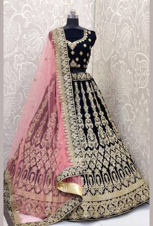 Be The Trendy Bride Wearing This Heavy designer Lehenga Choli In Navy Blue Color Paired With Contrasting Baby Pink Colored Dupatta. Its Blouse And Lehenga Are Fabricated On Velvet Paired With Net Fabricated Dupatta. Buy Now.