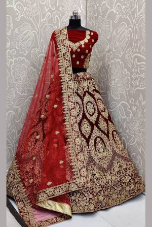 Be The Trendy Bride Wearing This Heavy designer Lehenga Choli In Maroon Color Paired With Red Colored Dupatta. Its Blouse And Lehenga Are Fabricated On Velvet Paired With Net Fabricated Dupatta. Buy Now.