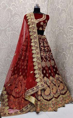 Here Is A Royal Looking Heavy Bridal Lehenga Choli In Maroon Color. Its Blouse And Lehenga Are Fabricated On Velvet Paired With Net Fabricated Dupatta. This Designer Heavy Bridal Lehenga Choli Has Attractive Peacock Motifs. Buy Now.
