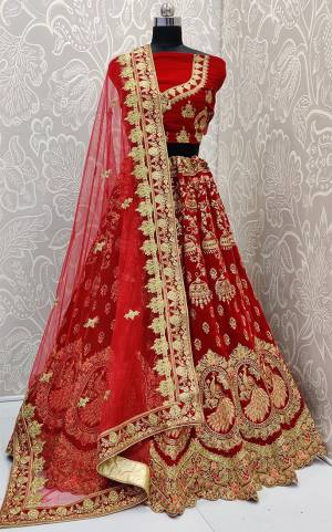 Here Is A Royal Looking Heavy Bridal Lehenga Choli In Red Color. Its Blouse And Lehenga Are Fabricated On Velvet Paired With Net Fabricated Dupatta. This Designer Heavy Bridal Lehenga Choli Has Attractive Peacock Motifs. Buy Now.