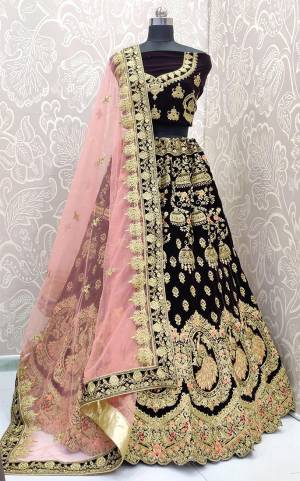 Here Is A Royal Looking Heavy Bridal Lehenga Choli In Wine Color Paired With Baby Pink Colored Dupatta. Its Blouse And Lehenga Are Fabricated On Velvet Paired With Net Fabricated Dupatta. This Designer Heavy Bridal Lehenga Choli Has Attractive Peacock Motifs. Buy Now.