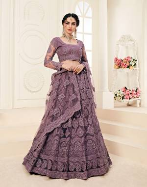 Get Ready For The Upcoming Wedding Season Wearing This Lovely Tone To Tone Heavy Embroidered Lehenga Choli In Dusty Purple Color. Its Blouse, Lehenga And Dupatta Are Fabricated On Net Which Comes With Same Colored Satin Silk Inner. Pair This Up With Delicate Pearl Accessories for A Look Like Never Before.