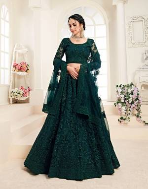 Flaunt Your Rich And Elegant Taste Wearing This Very Pretty Heavy Designer Lehenga Choli In All Over Dark Teal Green Color. This Pretty Lehenga Choli Is Fabricated On Net Paired With Net Fabricated Dupatta. It Is Beautified With Heavy Tone To Tone Embroidery Giving It A Pretty Subtle Yet Heavy Look.
