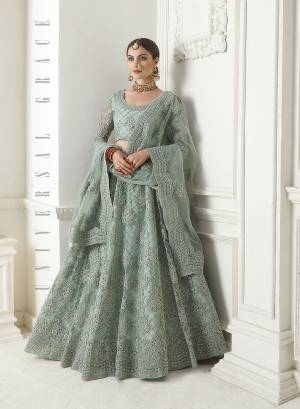Look Ravishing Wearing This Heavy Deisgner Lehenga Choli In All Over Dusty Green Color. Its Detailed Embroidered Blouse, Lehenga And Dupatta Are Fabricated Net Beautified With Elegant Tone To Tone Resham And Coding Work Highlited With Stones. Buy This Heavy Yet Subtle Look Designer Lehenga Choli Now.