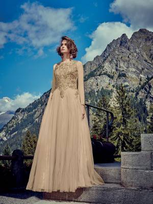 Flaunt Your Rich And Elegant Taste Wearing This Designer Readymade Gown In All Over Beige Color. This Pretty Attractive Gown Is Fabricated Net Beautified With Stone Work Paired With Chiffon Fabricated Dupatta. Buy Now.