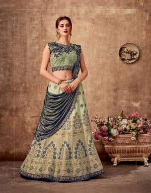 Embrace the very beauty of harmony in this pastel green and blue saree-lehenga ornamneted with stunning weaves and embroideries. Pair with subtle and simple jewels to make the most of this look.