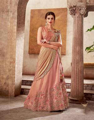 Exuding old-world charm and glamour in this Peach lehenga saree with just the right amount of sheen and shine fancied with tonal embroidery and appliqued flowers.