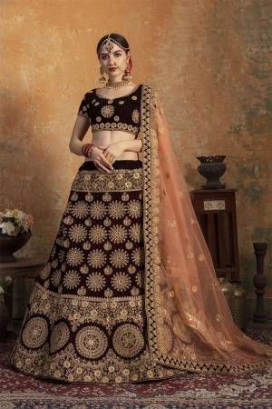 Here Is A Perfect Bridal Look For You In The Running Treand With This Heavy designer Lehenga Choli In Dark Maroon Color Paired With Contrasting Peach Colored Dupatta. This Lehenga Choli Is Velvet Based Paired With Net Fabricated Dupatta.Its Fabric Also Ensures Superb Comfort Throughout The Gala.