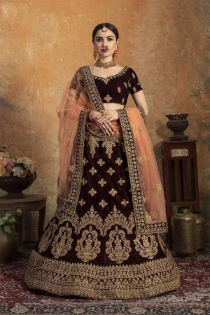 Get Ready For Your Big Day With This Latest Bridal Trend, Wearing This Heavy Designer Lehenga Choli In Dark Maroon Color Paired With Contrasting Peach Colored Dupatta. This Heavy Embroidered Lehenga Choli Is Fabricated On Velvet Paired With Net Fabricated Dupatta. It Is Beautified With Heavy Embroidery. Buy Now