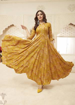 Celebrate This Festive Season With Beauty And Comfort Wearing This Designer Readymade Gown In Musturd Yellow Color Fabricated On Rayon. It Is Beautified With Prints. Buy Now.