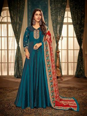 Get rEady For The Upcoming Festive And Weadding Season With This Designer Readymade Gown In Blue Color Paired With Red And Blue Colored Dupatta. This Gown Is Fabricated On Satin Georgette Paired With Muslin Fabricated Dupatta. Buy Now.