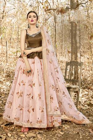 Here Is A Tendy Designer Lehenga Choli In Peplum Pattern With Brown Colored Blouse Paired With Contrasting Pastel Pink Colored Lehenga And Dupatta. Its Blouse Is Fabricated On Art Silk Paired With Orgenza Based Lehenga And Dupatta. Buy This Trendy Piece Now.