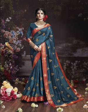 Get Ready For The Upcoming Wedding And Festive Season With This Designer Saree In Teal Blue Color. This Attractive Jari Embroidered Saree Is Fabricated On Vichitra Silk Paired With Vichitra Silk Fabricated Blouse. It Is Beautified With Broad Lace Border With Stone Work. Buy Now.