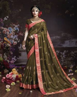 Get Ready For The Upcoming Wedding And Festive Season With This Designer Saree In Olive Green Color. This Attractive Jari Embroidered Saree Is Fabricated On Vichitra Silk Paired With Vichitra Silk Fabricated Blouse. It Is Beautified With Broad Lace Border With Stone Work. Buy Now.