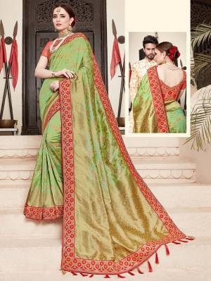 For A Proper Traditional Look, Grab This Heavy Designer Saree In Green Color Paired With Contrasting Peach Colored Blouse. This Saree Is Fabricated On Jacquard Silk Paired With Art Silk Fabricated Blouse. It Is Beautified With Heavy Embroidered Lace Border And Blouse.