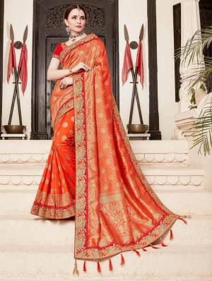 For A Proper Traditional Look, Grab This Heavy Designer Saree In Orange Color Paired With Contrasting Red Colored Blouse. This Saree Is Fabricated On Jacquard Silk Paired With Art Silk Fabricated Blouse. It Is Beautified With Heavy Embroidered Lace Border And Blouse.