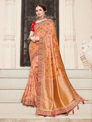 For A Proper Traditional Look, Grab This Heavy Designer Saree In Peach Color Paired With Contrasting Red Colored Blouse. This Saree Is Fabricated On Jacquard Silk Paired With Art Silk Fabricated Blouse. It Is Beautified With Heavy Embroidered Lace Border And Blouse.