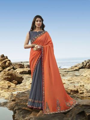 Celebrate this Festive Season Wearing This Attractive Heavy Designer Saree In Orange & Dark Grey Color Paired With Dark Grey Colored Blouse. This Saree Is Soft Silk Based Which Gives A Rich Look To Your Personality.
