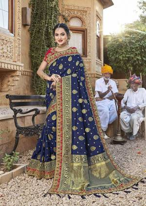 For A Royal Look, Grab This Designer Saree In Navy Blue Color Paired With Contrasting Dark Pink Colored Blouse. This Saree Is Fabricated On Satin Jacquard Silk Paired With Art Silk Fabricated Blouse. It Is Beautified With Attractive Embroidered Lace Border And Blouse.