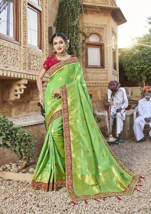 For A Royal Look, Grab This Designer Saree In Green Color Paired With Contrasting Dark Pink Colored Blouse. This Saree Is Fabricated On Satin Jacquard Silk Paired With Art Silk Fabricated Blouse. It Is Beautified With Attractive Embroidered Lace Border And Blouse.