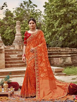 Celebrate This Festive And Wedding Season With This Heavy Designer Saree In Orange Color Paired With Contrasting Red Colored Blouse. This Pretty Saree Is Fabricated On Jacquard Silk Paired With Art Silk Fabricated Blouse.