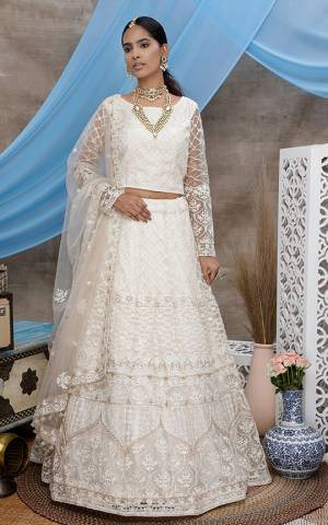 You Will Definitely Earn Lots Of Compliments Wearing This Heavy Designer Lehenga Choli In All Over Off-White Color. Its Pretty Blouse, Lehenga and Dupatta Are Fabricated On Net Beautified with Tone To Tone Thread Embroidery And Stone Work. Buy This Elegant Peice Now.