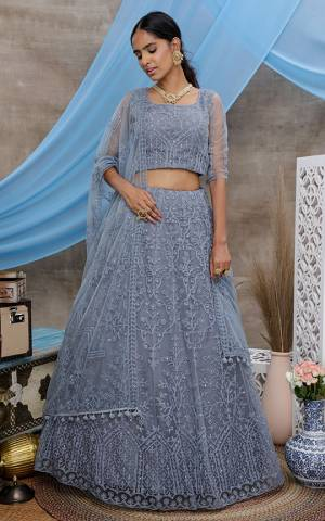 You Will Definitely Earn Lots Of Compliments Wearing This Heavy Designer Lehenga Choli In All Over Grey Color. Its Pretty Blouse, Lehenga and Dupatta Are Fabricated On Net Beautified with Tone To Tone Thread Embroidery And Stone Work. Buy This Elegant Peice Now.