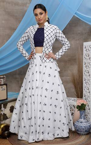 Here Is A Rich And Elegant Looking Lehenga Choli Which Comes With A Jacket. Its Attractive Blouse Is In Navy Blue Color Paired With White Colored Lehenga And Jacket. This Whole Pair Of Lehenga, Choli And Jacket Are Cotton Based, Beautified With Pretty Work.