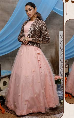 Catch All The Limelight At The Next Wedding You Attend Wearing This Designer Lehenga Choli In Pretty Peach Color Paired With Copper Colored Heavy Sequence Work Jacket. Its Pretty Blouse And Lehenga Are Net Based Paired With Velvet Fabricated Jacket.