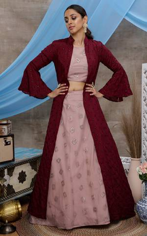 You Will Definitely Earn Lots Of Compliments Wearing This Designer IndoWestern Lehenga Choli In Dusty Pink Color Paired With Contrasting Maroon Colored Jacket. Its Elegant Embroidered Blouse and Lehenga Are Fabricated On Net Paired With Chinon Fabricated Jacket.
